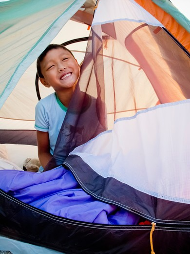 Young boy peeking out from tent on beach at sunrise, : Stock Photo