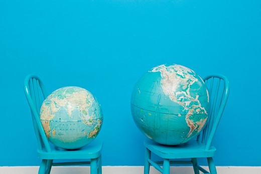 Two globes placed on two chairs facing each other, : Stock Photo