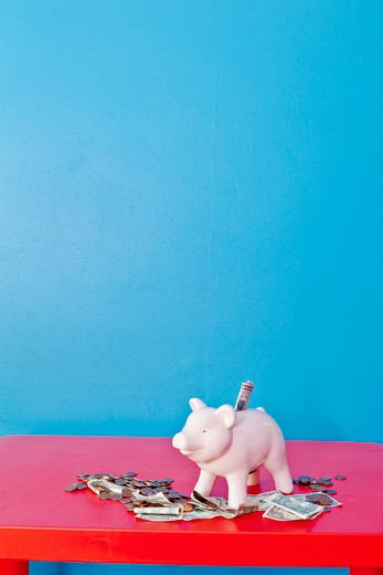 Stock Photo: 1530R-41866 Piggy bank on red table,