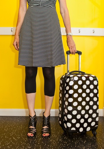 Stock Photo: 1530R-41873 Woman standing next to polka dot suitcase,