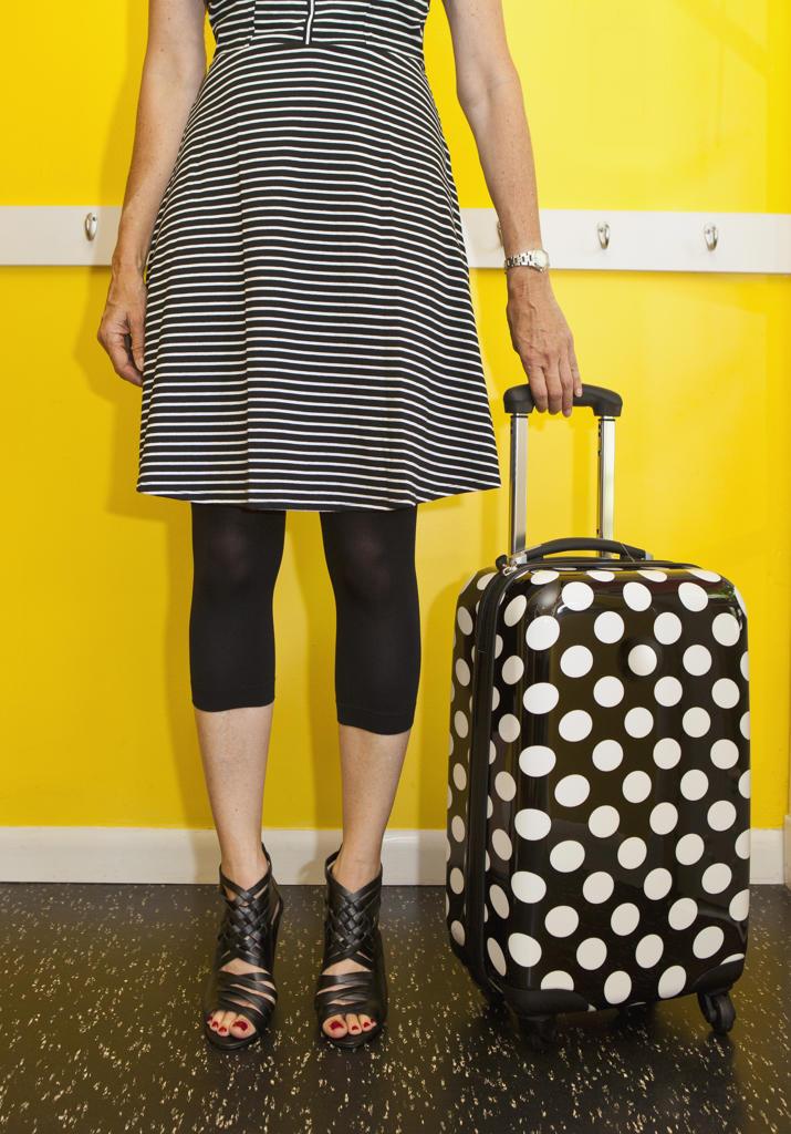 Woman standing next to polka dot suitcase, : Stock Photo