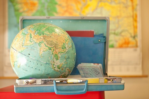 Globe sitting inside open vintage briefcase : Stock Photo