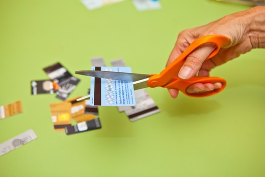 Stock Photo: 1530R-41891 Hand using scissors to cut up credit cards