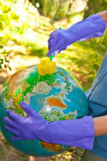Stock Photo: 1530R-41892 Woman wearing rubber gloves to scrub globe outdoors