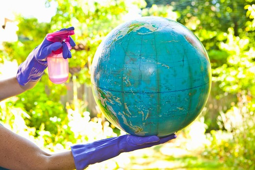 Stock Photo: 1530R-41893 Woman wearing rubber gloves to clean globe outdoors