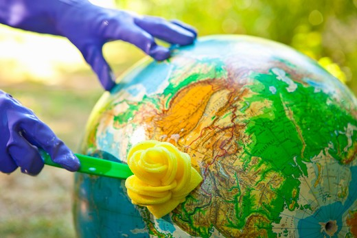Woman wearing rubber gloves to scrub globe outdoors : Stock Photo