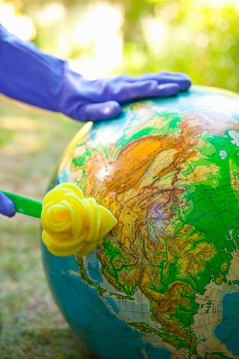 Stock Photo: 1530R-41895 Woman wearing rubber gloves to scrub globe outdoors