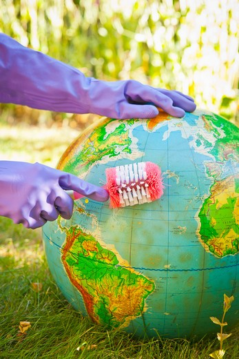 Stock Photo: 1530R-41897 Woman wearing rubber gloves to scrub globe outdoors