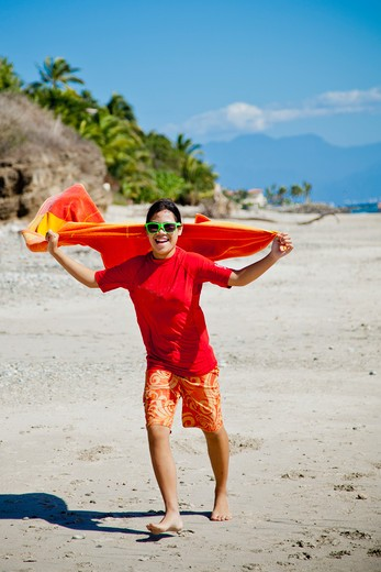 Stock Photo: 1530R-41901 Teen girl running on beach with towel cape