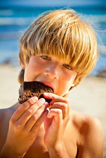 Young boy taking bite of large brownie : Stock Photo