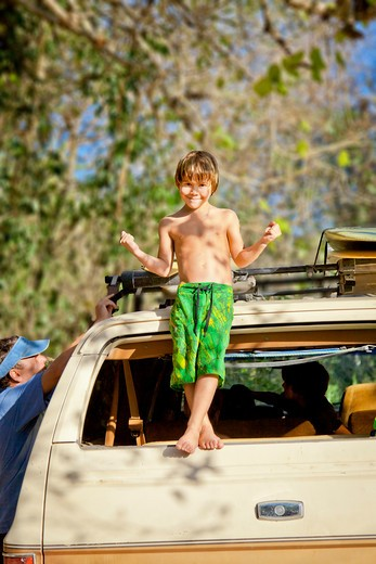 Boy standing on back of car : Stock Photo