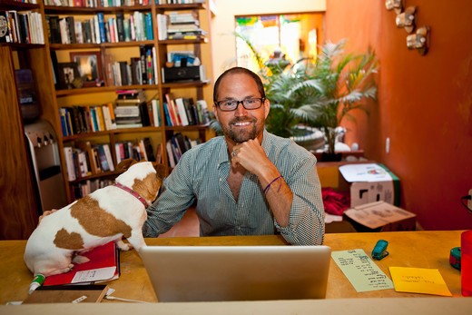 Stock Photo: 1530R-41910 Man seated at home office with dog on desk