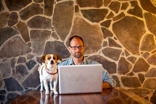 Stock Photo: 1530R-41916 Man seated at long table with laptop and dog