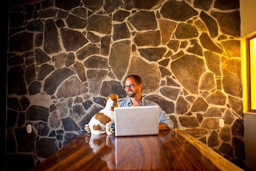 Stock Photo: 1530R-41917 Man seated at long table with laptop and dog
