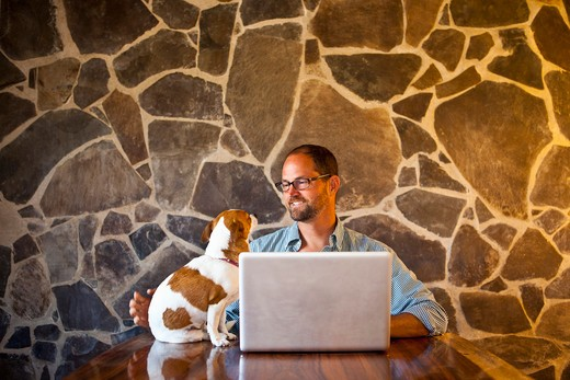 Man seated at long table with laptop and dog : Stock Photo