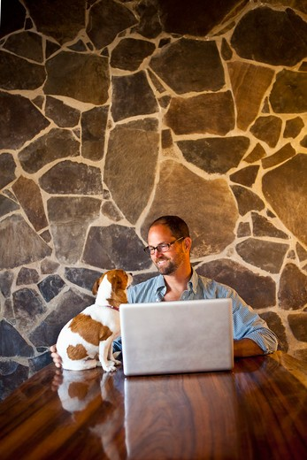 Stock Photo: 1530R-41919 Man seated at long table with laptop and dog