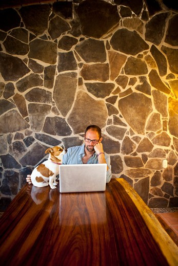 Stock Photo: 1530R-41921 Man seated at long table with laptop and dog