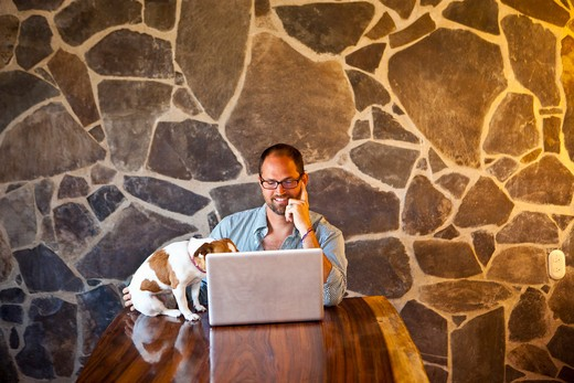 Stock Photo: 1530R-41922 Man seated at long table with laptop and dog