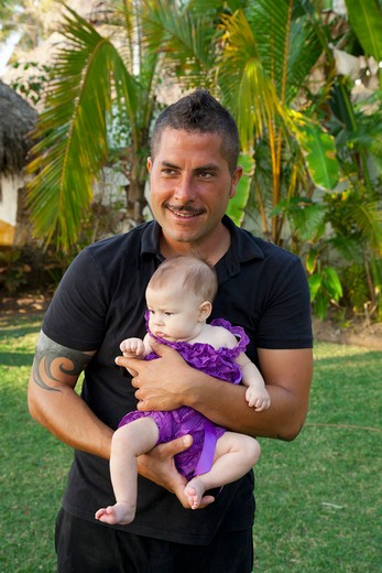 Stock Photo: 1530R-41926 Man in black clothing holding baby girl