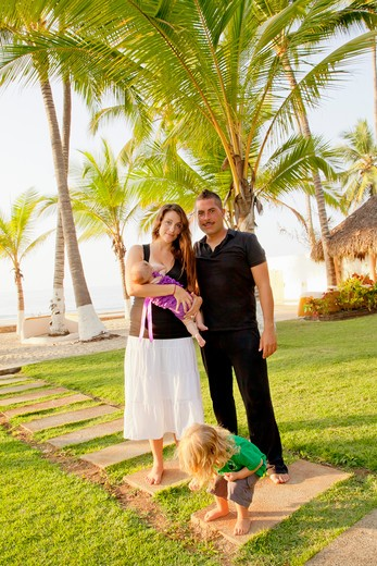 Stock Photo: 1530R-41938 Portrait of young family in front of beach side palms