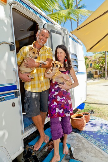 Stock Photo: 1530R-41963 Man and woman holding small dogs on camper steps,  Sayulita, Mexico