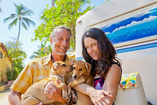 Man and woman holding small dogs at rear of camper,  Sayulita, Mexico : Stock Photo