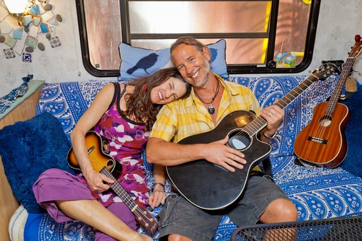 Stock Photo: 1530R-41966 Man and woman cuddling on sofa in camper with guitars,  Sayulita, Mexico