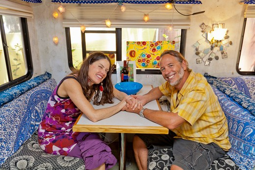 Stock Photo: 1530R-41968 Man and woman holding hands at camper table,  Sayulita, Mexico