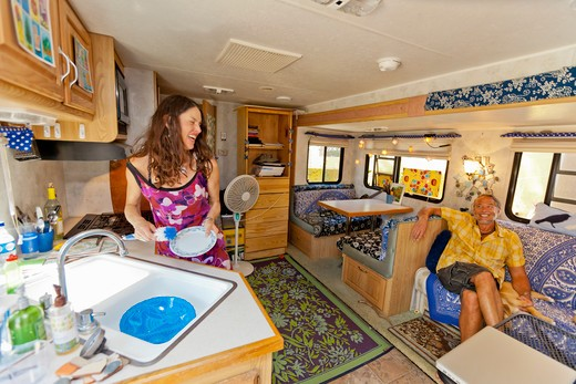 Stock Photo: 1530R-41970 Woman washing dishes in camper while man watches,  Sayulita, Mexico