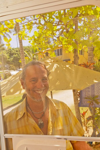 Stock Photo: 1530R-41972 Man looking in from outdoors through camper screen door,  Sayulita, Mexico