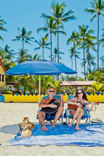 Happy man and woman in beach chairs with guitars and dogs,  Sayulita, Mexico : Stock Photo