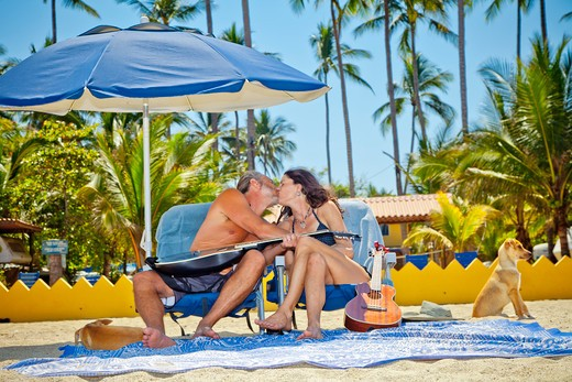 Stock Photo: 1530R-41981 Man and woman kissing while seated in beach chairs,  Sayulita, Mexico
