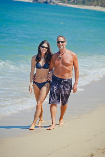 Stock Photo: 1530R-41986 Man and woman walking on beach in swim suits,  Sayulita, Mexico