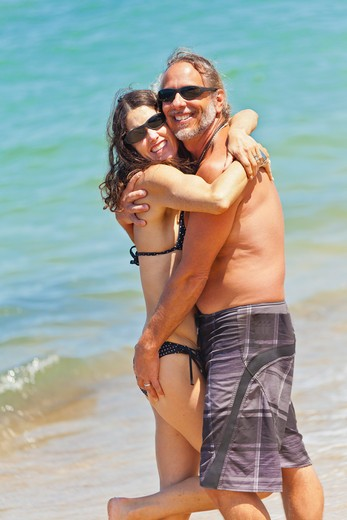 Stock Photo: 1530R-41987 Man and woman embracing on beach in swim suits,  Sayulita, Mexico