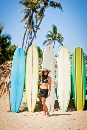 Woman in swimsuit in front of row of surfboards,  Sayulita, Mexico : Stock Photo