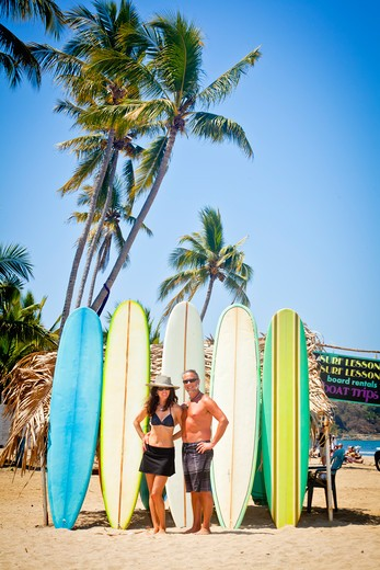 Stock Photo: 1530R-41990 Man and woman in swimsuits in front of row of surfboards,  Sayulita, Mexico