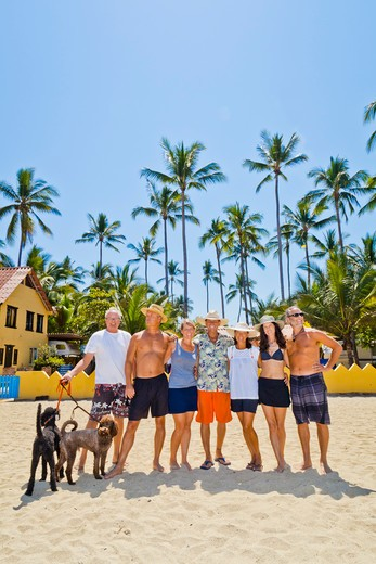 Seven adults standing on beach with dogs near palm trees,  Sayulita, Mexico : Stock Photo