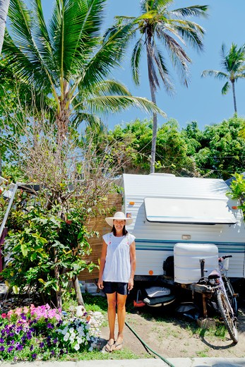 Stock Photo: 1530R-41996 Woman standing in garden with camper,  Sayulita, Mexico