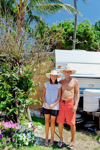 Stock Photo: 1530R-41997 Man and woman standing in garden with camper,  Sayulita, Mexico