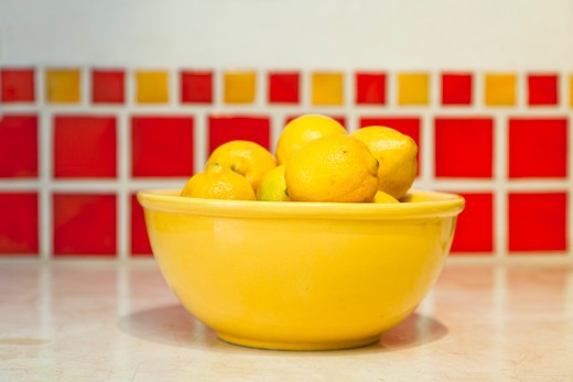 Stock Photo: 1530R-42026 Bowl of lemons on counter with red tiles behind