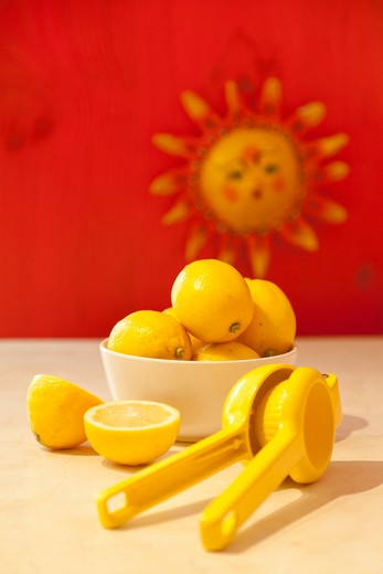 Stock Photo: 1530R-42032 Bowl of lemons and lemon juicer on counter