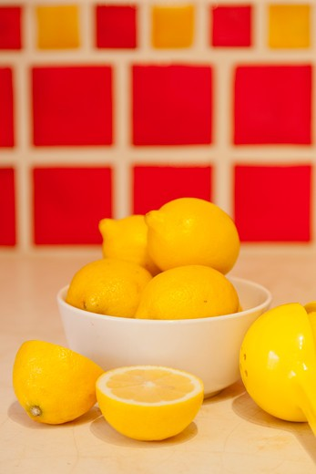 Bowl of lemons on counter with red tiles behind : Stock Photo