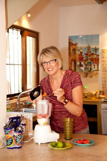 Stock Photo: 1530R-42034 Woman making smoothie in kitchen blender