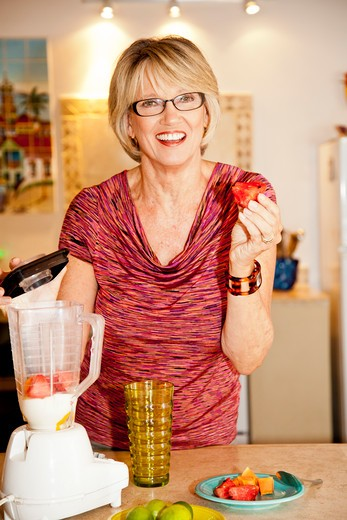 Woman making smoothie in kitchen blender : Stock Photo