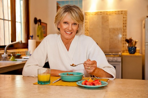 Woman seated at counter eating healthy breakfast : Stock Photo