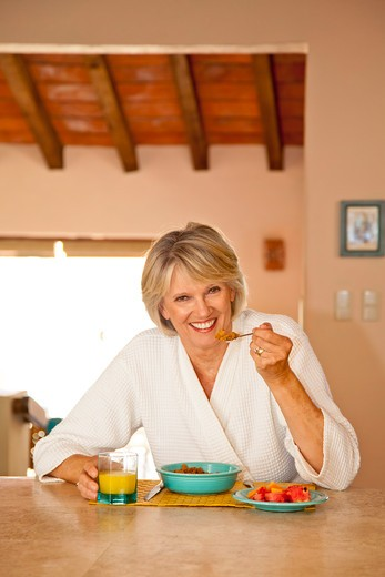 Stock Photo: 1530R-42044 Woman seated at counter eating healthy breakfast