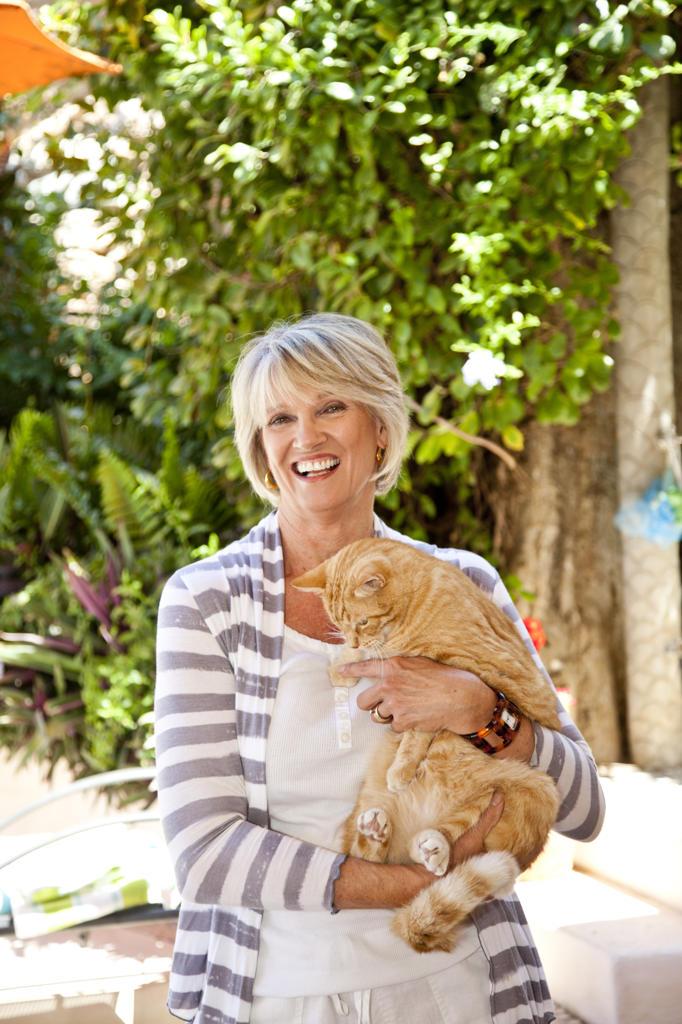 Woman holding orange cat on patio : Stock Photo