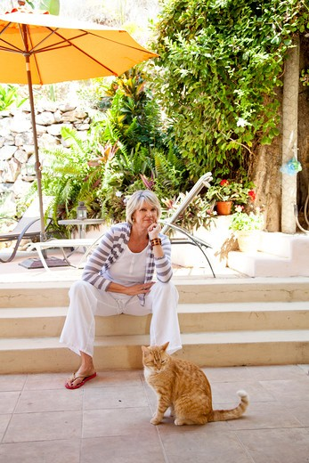 Stock Photo: 1530R-42048 Woman seated on patio steps with orange cat