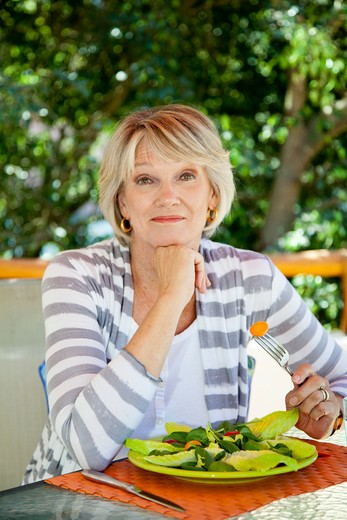 Stock Photo: 1530R-42051 Woman eating salad outdoors