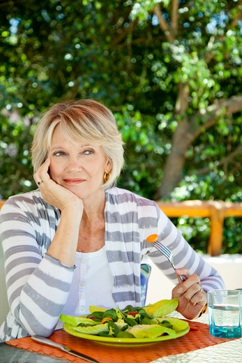 Woman eating salad outdoors : Stock Photo